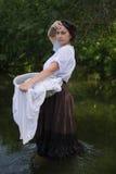 La mujer campesina lava la ropa en el río Fotografía de archivo libre de regalías