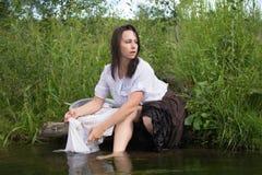 La mujer campesina lava la ropa en el río Fotografía de archivo