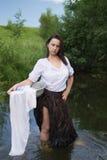 La mujer campesina lava la ropa en el río Imagen de archivo libre de regalías