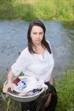 La mujer campesina lava la ropa en el río Imágenes de archivo libres de regalías