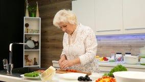 La mujer canosa madura cortó los tomates de cereza para una ensalada en la cocina almacen de metraje de vídeo