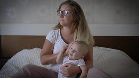 La mujer cansada del trastorno con dolor de cabeza detiene al bebé en las manos que se sientan en cama en casa metrajes