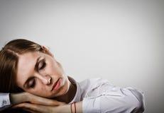 La mujer cansada en blanco está durmiendo imagen de archivo