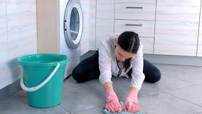 La mujer cansada en guantes de goma rosados lava y frota difícilmente el piso de la cocina con un paño Tejas grises en el piso metrajes