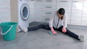 La mujer cansada en guantes de goma rosados lava y frota difícilmente la mancha en piso de la cocina con un paño Tejas grises en  almacen de metraje de vídeo