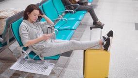 La mujer cansada está descansando en un asiento del pasillo que espera en aeropuerto, introdujo las piernas en su maleta amarilla almacen de metraje de vídeo