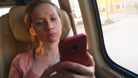 La mujer cansada monta el autobús usando su teléfono foto de archivo libre de regalías