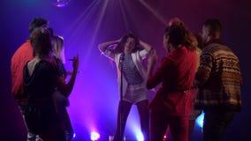 La mujer canta retro un micrófono que se realiza en etapa como danzas de la audiencia en estudio del humo Fume el fondo Cámara le metrajes