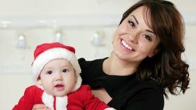 La mujer cariñosa con un bebé, madre feliz con su hijo joven en sus brazos, divirtiéndose que juega, familia feliz celebra nuevo almacen de video
