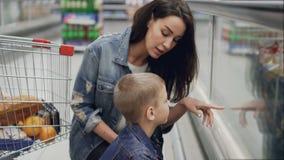 La mujer cariñosa está eligiendo el helado en el congelador para su pequeño hijo lindo que mira la comida a través del vidrio que metrajes