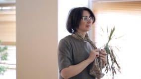 La mujer casada de moda morena explica cómo atar la bufanda de seda almacen de metraje de vídeo