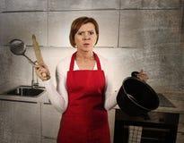 La mujer casera del cocinero confundida y frustrada en el delantal que pide la ayuda sucia corrige Foto de archivo libre de regalías