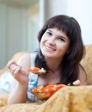 La mujer casual come la ensalada de los tomates fotografía de archivo libre de regalías