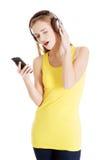 La mujer casual hermosa en top del amarillo está escuchando la música. Foto de archivo