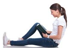 La mujer casual pone en piso y lee Fotografía de archivo