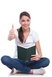 La mujer casual se sienta con el libro y la autorización Imagenes de archivo