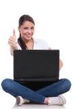 La mujer casual se sienta con el ordenador portátil y la autorización Fotos de archivo libres de regalías
