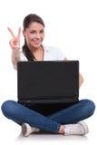 La mujer casual se sienta con el ordenador portátil y la victoria Imágenes de archivo libres de regalías