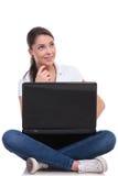 La mujer casual se sienta con el ordenador portátil y piensa Imagen de archivo libre de regalías