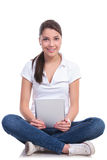 La mujer casual se sienta con la tableta Imágenes de archivo libres de regalías