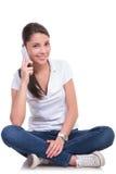 La mujer casual se sienta y habla en el teléfono Foto de archivo libre de regalías