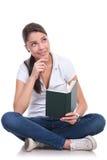 La mujer casual se sienta y lee y piensa Fotos de archivo libres de regalías