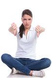 La mujer casual se sienta y manosea con los dedos Foto de archivo