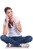 La mujer casual se sienta y piensa en el teléfono Foto de archivo libre de regalías