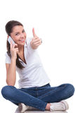 La mujer casual se sienta y pulgar para arriba en el teléfono Fotografía de archivo libre de regalías