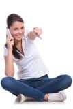La mujer casual se sienta y señala en el teléfono Fotografía de archivo