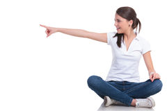 La mujer casual sienta y señala el lado Imagen de archivo libre de regalías