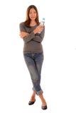 La mujer casual sonriente es permanente y que lleva a cabo una botella de wate Foto de archivo libre de regalías