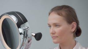 La mujer caucásica con el espejo con la luz del anillo sin mirada del maquillaje examina su piel y hace el tratamiento facial almacen de metraje de vídeo