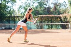 La mujer caucásica con el pelo rubio está jugando al tenis al aire libre Visión desde la parte posterior Imagenes de archivo