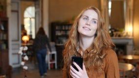 La mujer caucásica del pelo rojo joven escucha la música en el teléfono y danzas en café almacen de video