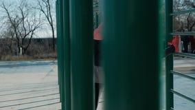 La mujer caucásica del tiro de la cacerola estira al aire libre en las barras de tierra de deportes en invierno