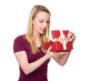 La mujer caucásica desempaqueta de la caja de regalo Fotos de archivo libres de regalías