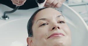 La mujer caucásica en salón tiene un tratamiento del pelo con el aparador profesional del pelo metrajes