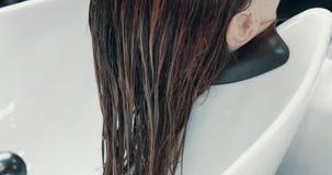 La mujer caucásica en salón tiene un tratamiento del pelo con el aparador profesional del pelo almacen de video