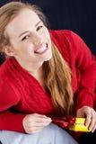 La mujer caucásica hermosa en suéter rojo es unwrappind pequeño pre Fotos de archivo