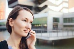 La mujer caucásica hermosa joven en ropa del estilo sport está hablando en su teléfono móvil que se coloca cerca de los edificios Imagen de archivo