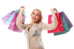 La mujer caucásica hermosa joven sostiene bolsos de compras coloridos y Foto de archivo libre de regalías