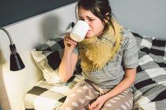 La mujer caucásica hermosa joven tiene un frío, gripe con alta fiebre y calor en casa en cama La muchacha toma píldoras del dolor imagen de archivo libre de regalías