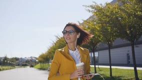 La mujer caucásica joven bonita en traje y gafas de sol es mantiene un dispositivo de la tableta manos que bebe el café en el mod almacen de video