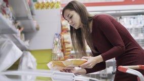 La mujer caucásica joven elige las comidas congeladas del refrigerador en supermercado almacen de metraje de vídeo