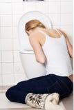 La mujer caucásica joven está vomitando en el cuarto de baño. Fotos de archivo libres de regalías