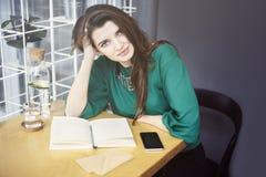 La mujer caucásica joven hermosa alrededor de sentarse treinta feliz en café, desayunando, bebe el waterÑŽ puro Fotos de archivo