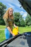 La mujer caucásica joven llena el motor del coche de aceite Foto de archivo