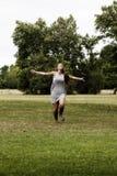 La mujer caucásica joven que corre en hierba verde arma extendido Foto de archivo