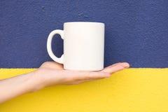 La mujer caucásica joven sostiene a mano la taza blanca de la maqueta en blanco de la palma en la pared pintada amarillo azul mar Foto de archivo libre de regalías